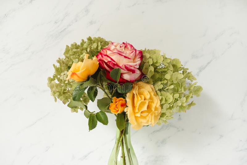 Beautiful bouquet of red and yellow roses, green hydrangea in front of pale marble background. Floral lifestyle composition. Beautiful bouquet of red and yellow royalty free stock photography