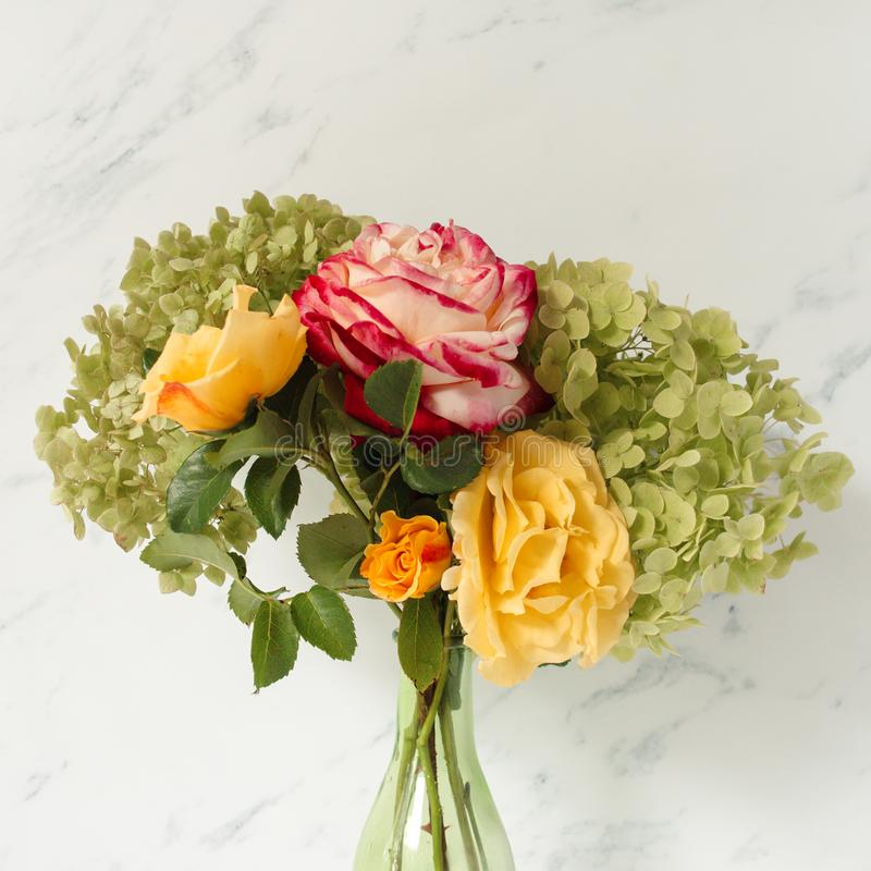 Beautiful bouquet of red and yellow roses, green hydrangea in front of pale marble background. Floral lifestyle composition. Beautiful bouquet of red and yellow stock photos