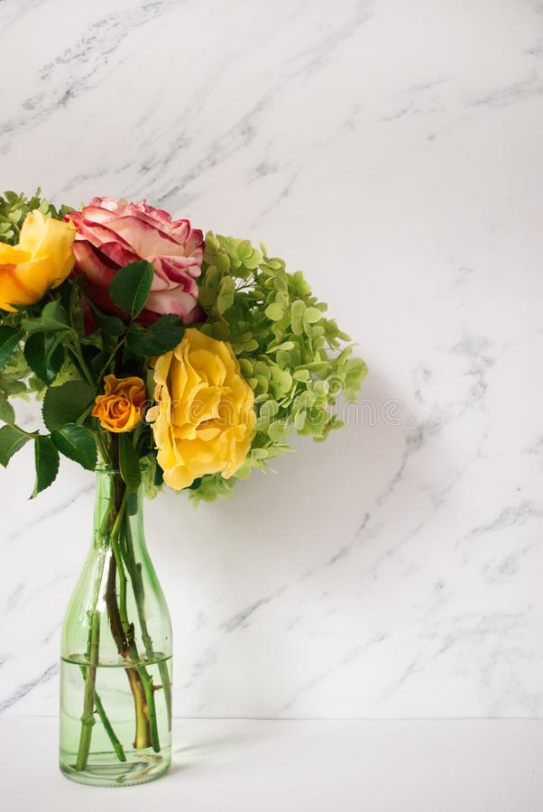 Beautiful bouquet of red and yellow roses, green hydrangea in front of pale marble background. Floral lifestyle composition with c. Opy space royalty free stock photo