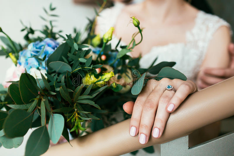 Beautiful bouquet of roses and bride`s hand with ring royalty free stock image