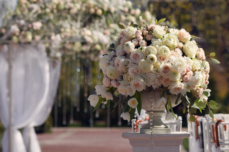 Beautiful bouquet of roses in a vase on a background of a wedding arch. Beautiful set up for the wedding ceremony. royalty free stock image