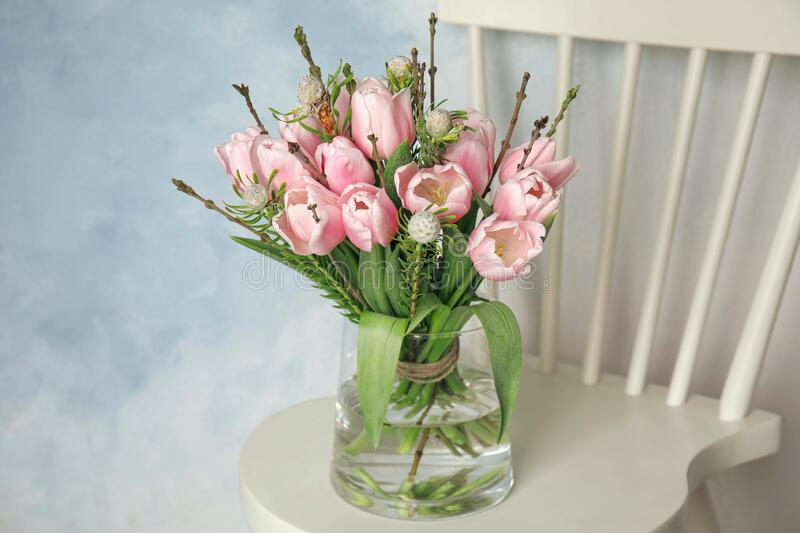 Beautiful bouquet with spring pink tulips on white chair stock photo