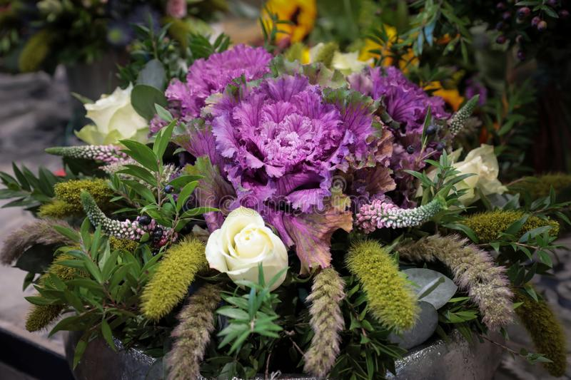 Beautiful bouquet of violet decorative cabbage Brassica oleracea var. acephala with different flowers. royalty free stock photos