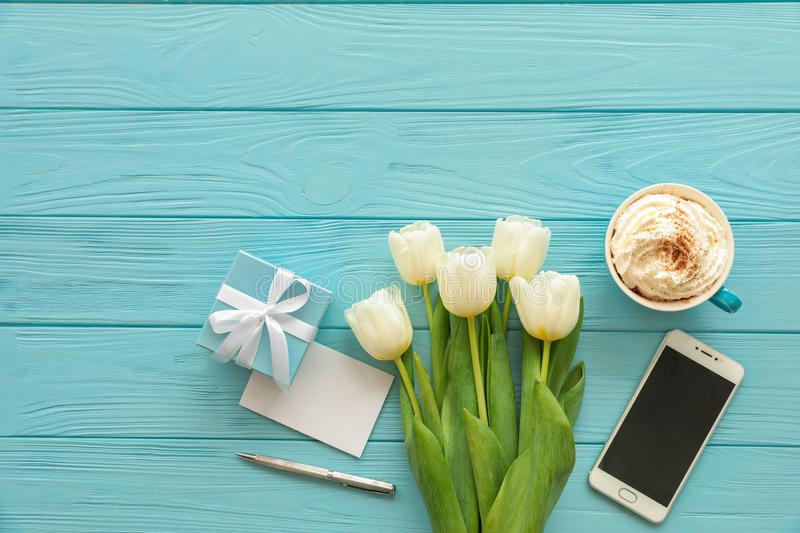 Beautiful bouquet of white tulips, blue gift box, cup of cappuccino, mobile phone on the blue wooden background with copy space, royalty free stock image