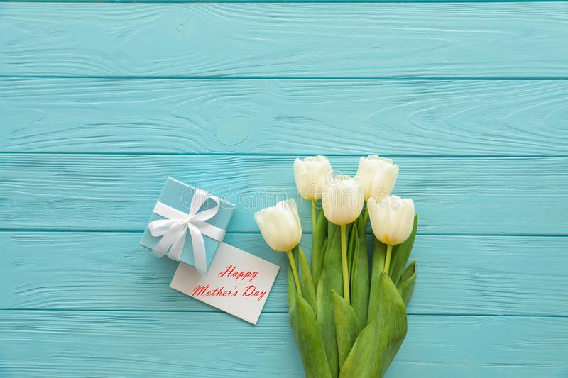 Beautiful bouquet of white tulips and a gift in a blue box with a white bow next to greeting card with text Happy Mother`s Day on stock images