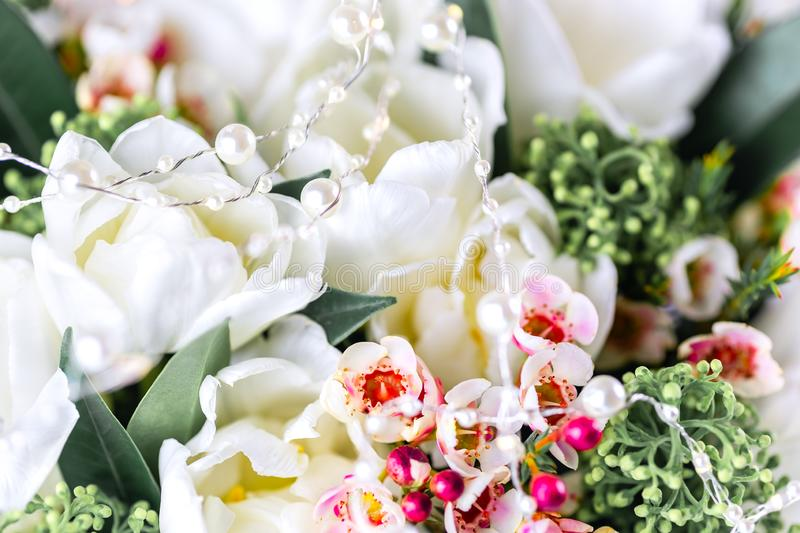 Beautiful bouquet of white tulips with green leaves and other decorative flowers close up. Beautiful bouquet of white tulips with green leaves and other stock image