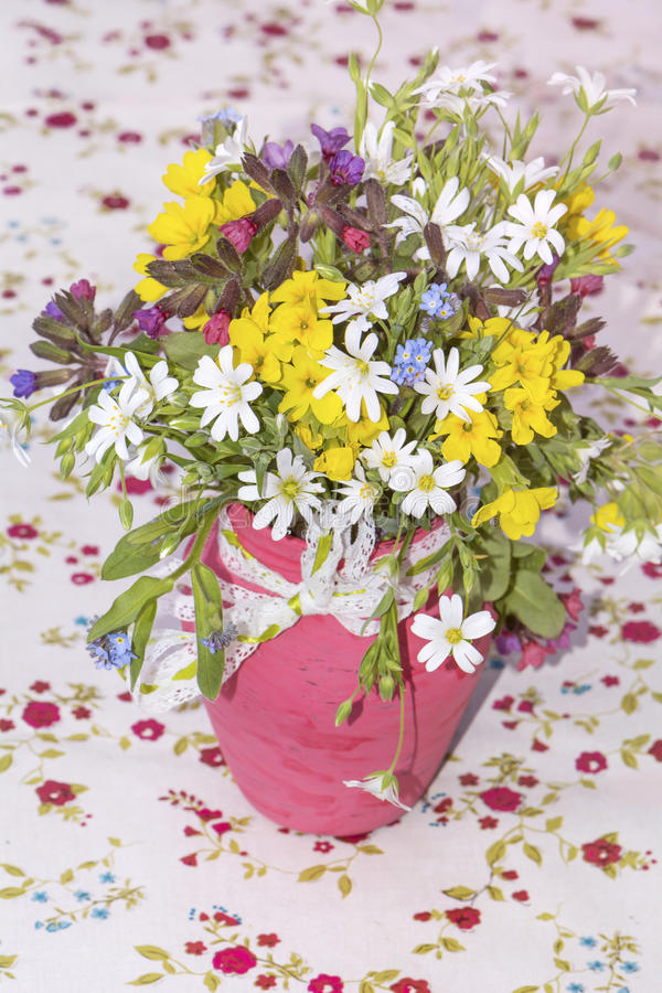 Beautiful bouquet with wild flowers in pink vase with ribbon stock images