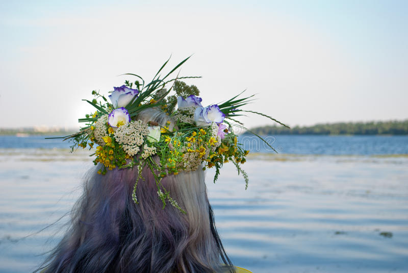 Beautiful bouquet of wreath of wild flowers on the head of a girl near the water river. One big beautiful bouquet wreath of wild flowers with yellow white and royalty free stock images