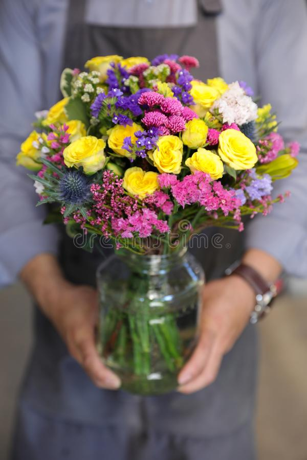 Beautiful bouquet in yellow, pink, blue colors of roses, statice and other flowers in the male florist hands. Vertical. Close-up stock images