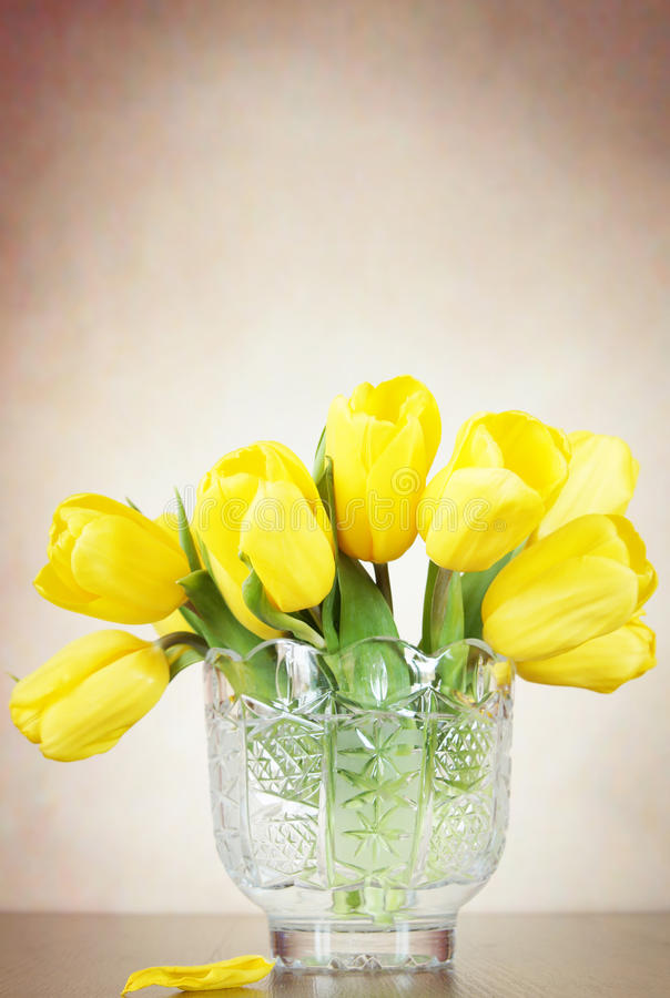 Beautiful bouquet of yellow tulip flowers stands in the crystal vase royalty free stock images