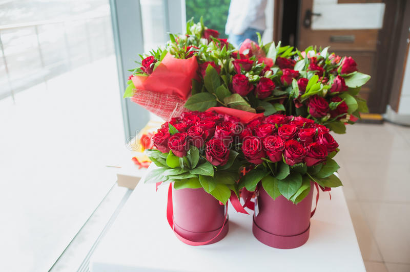 Beautiful bouquets of red roses in gift box, on white window sill stock photos