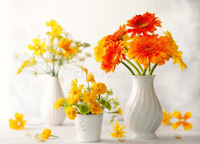Beautiful bouquet of red and yellow flowers in white vase on wooden table, front view. Autumn still life with flowers royalty free stock images