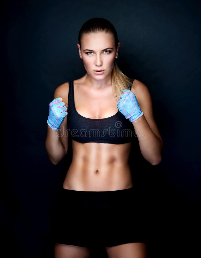 Beautiful boxer girl. Wearing sportive clothing and gloves practicing in the studio over black background, perfect athletic body, healthy lifestyle royalty free stock images