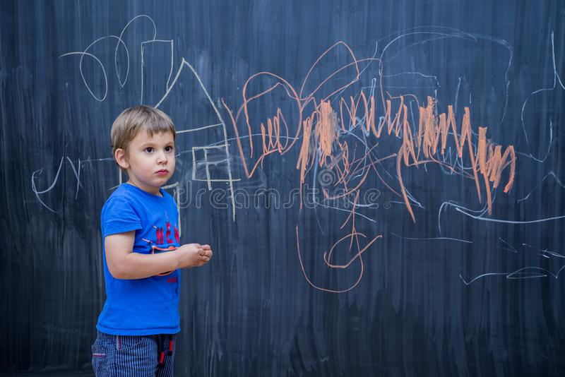 Beautiful boy drawing on a blackboard. Young artist concept stock photography