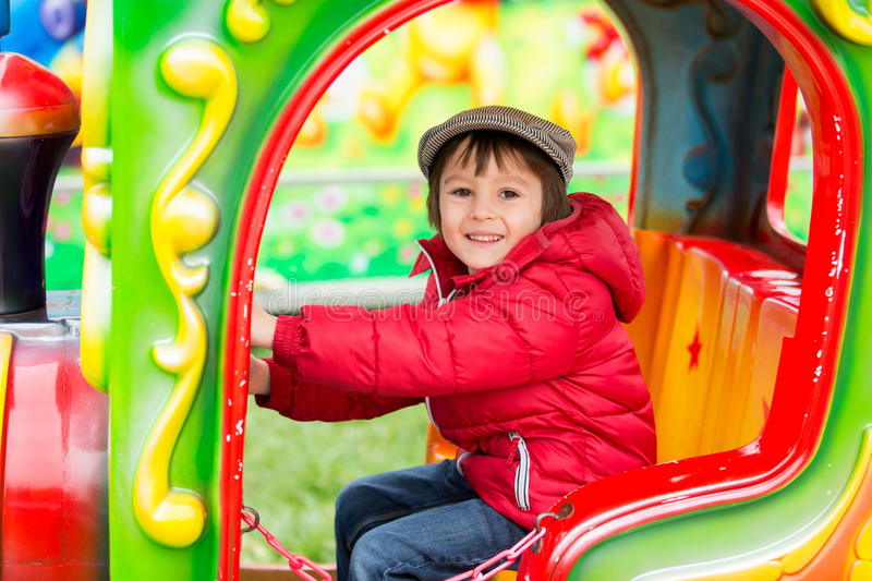 Beautiful boy having fun on the ride at the amusement park royalty free stock images