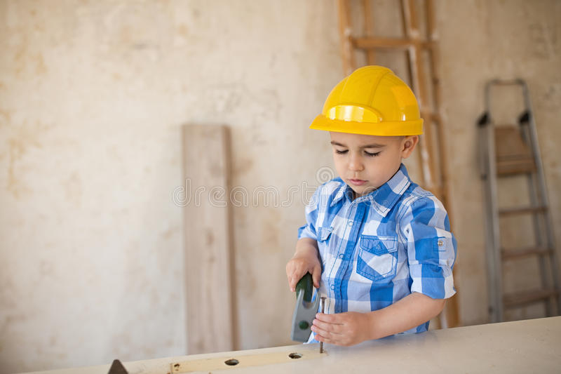 Beautiful boy knocks a nail with a hammer stock images