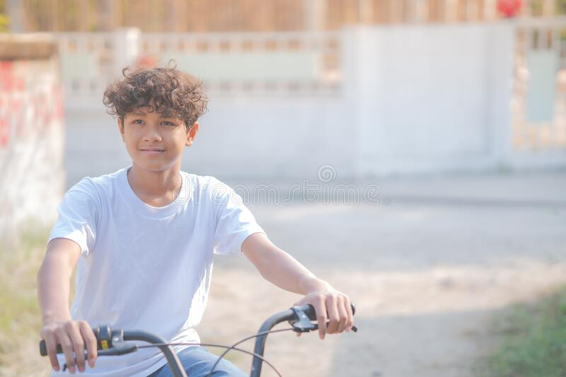 A beautiful boy rides a bicycle along his house stock images