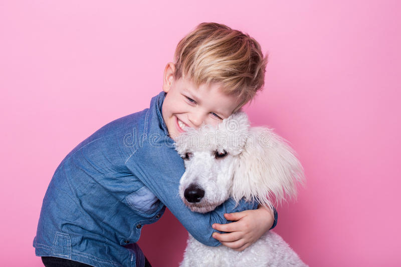 Beautiful boy with Royal Standard Poodle. Studio portrait over pink background. Concept: friendship between boy and his dog. Beautiful boy with Royal Standard royalty free stock photos