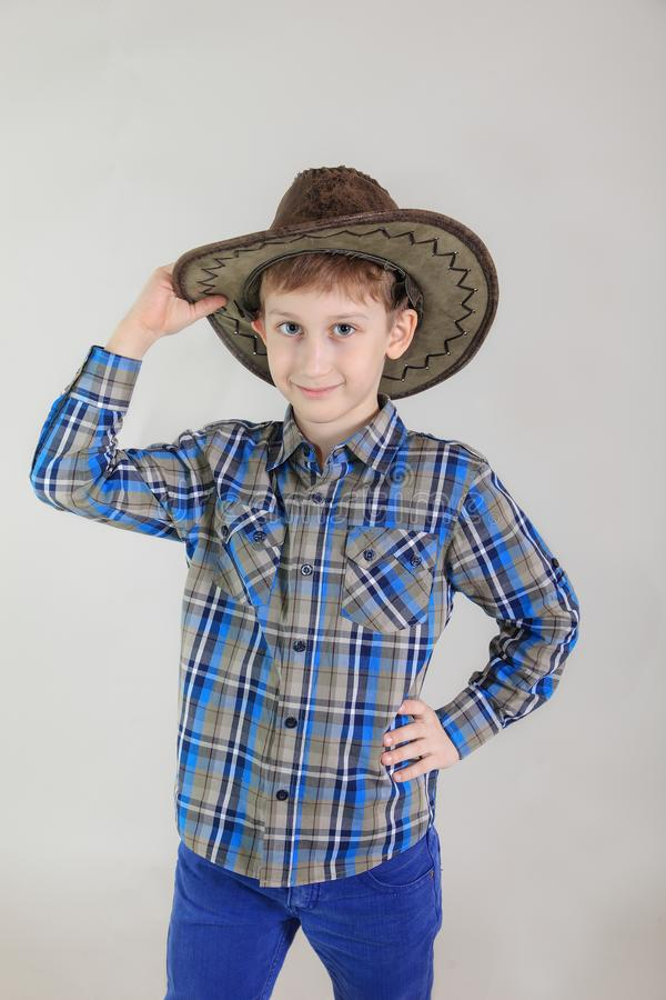 Portrait of cute Caucasian boy, elementary school student in cowboy hat on grey background . child aged 7 years first grader. stock photos