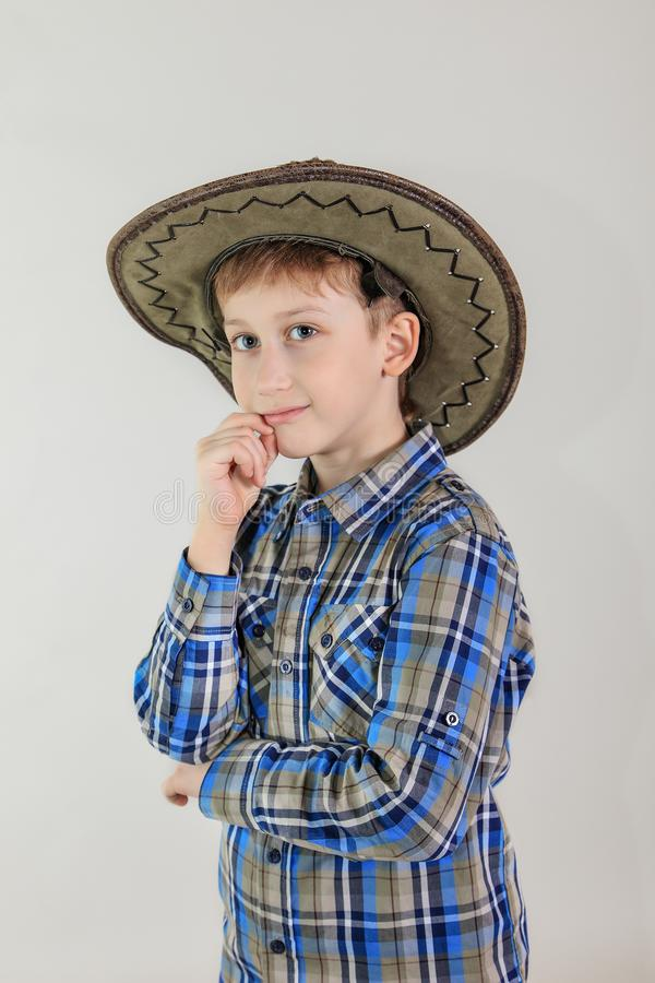 Portrait of cute Caucasian boy, elementary school student in cowboy hat on grey background . child aged 7 years first grader. royalty free stock images