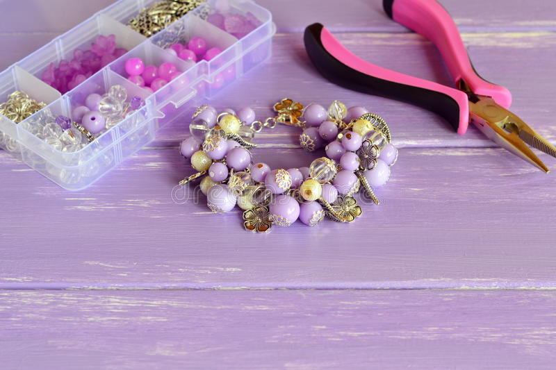 Beautiful bracelet with lilac and white plastic beads, metal flowers and leaves. Stylish accessory for girls and women. Organizer with different beads, steel royalty free stock image