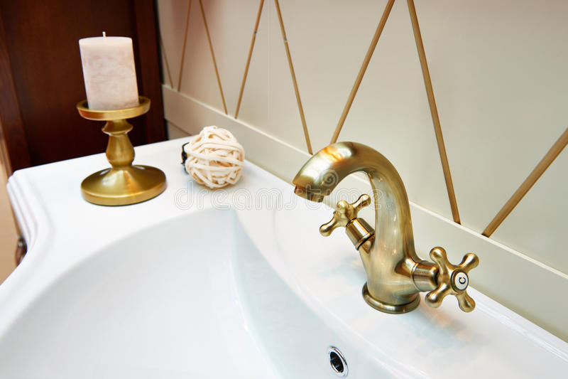 Beautiful brass faucet in retro and white sink royalty free stock photography