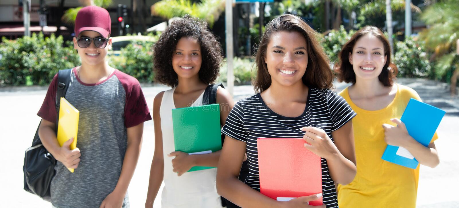 Beautiful brazilian female student with group of international s. Tudents outdoor in the city in the summer royalty free stock photos