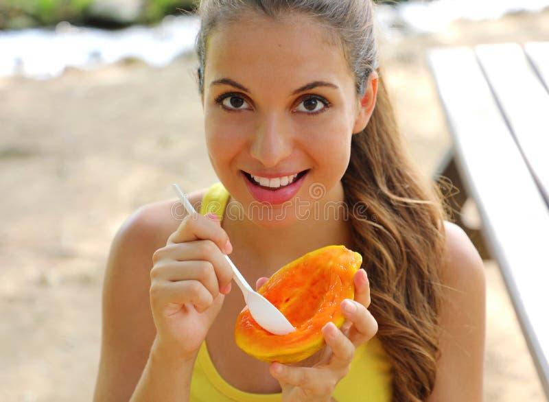Beautiful brazilian woman eating papaya fruit outdoor royalty free stock photos