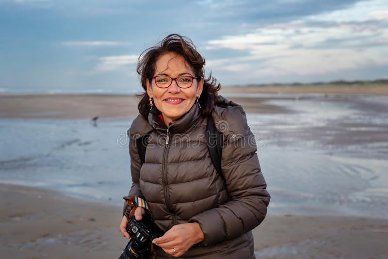 Beautiful middle-aged woman with glasses holding a camera on the beach, smiling and looking at the camera royalty free stock photography