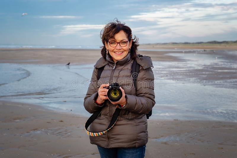 Beautiful middle-aged woman with glasses holding a camera on the beach, smiling and looking at the camera stock photo