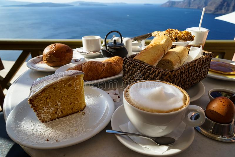 Beautiful breakfast with Aegean sea view and morning sunlight including cappuccino cup, cake, baguette, croissant, boiled egg stock images