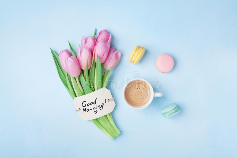 Beautiful breakfast on Mothers or Womans day. Coffee cup with pink tulip flowers, macaroon and note good morning on blue table. Beautiful breakfast on Mothers stock images