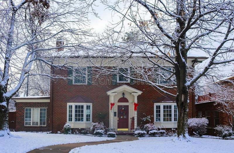 Beautiful brick house with bay windows with Christmas tree showing through and decorated pillars and sled on porch in snow framed. By winter trees royalty free stock images