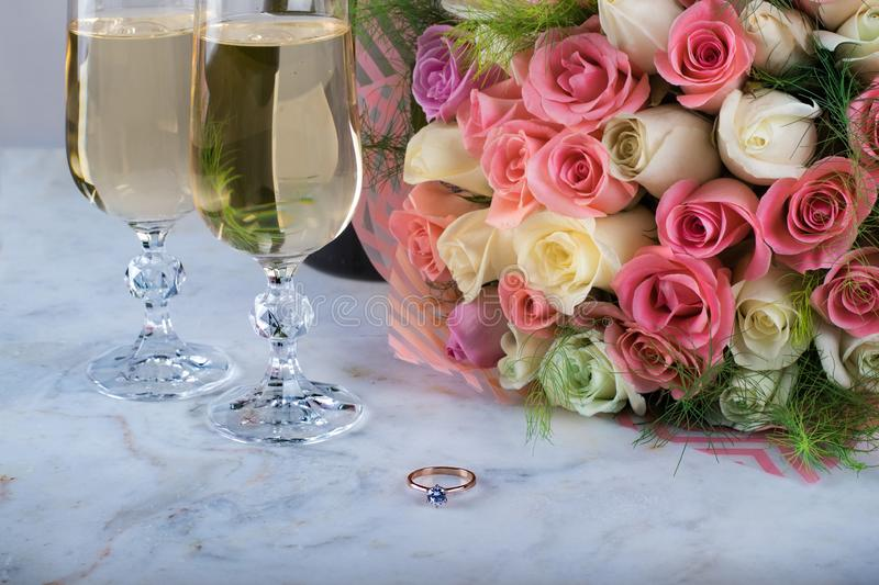A beautiful bridal bouquet of delicate roses, a ring with a diamond, two glasses of champagne on a marble table. Festive day, royalty free stock photos
