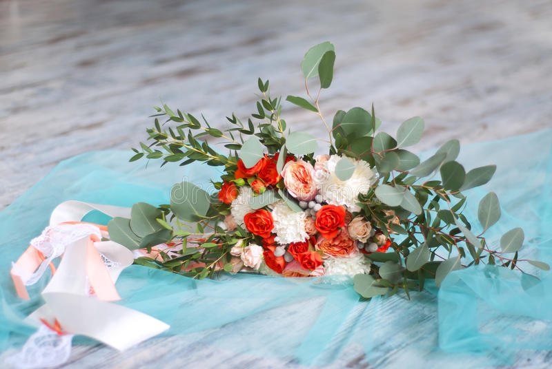 Beautiful bridal bouquet made of white and orange flowers. Ribbon and eucalyptus leaves royalty free stock photography