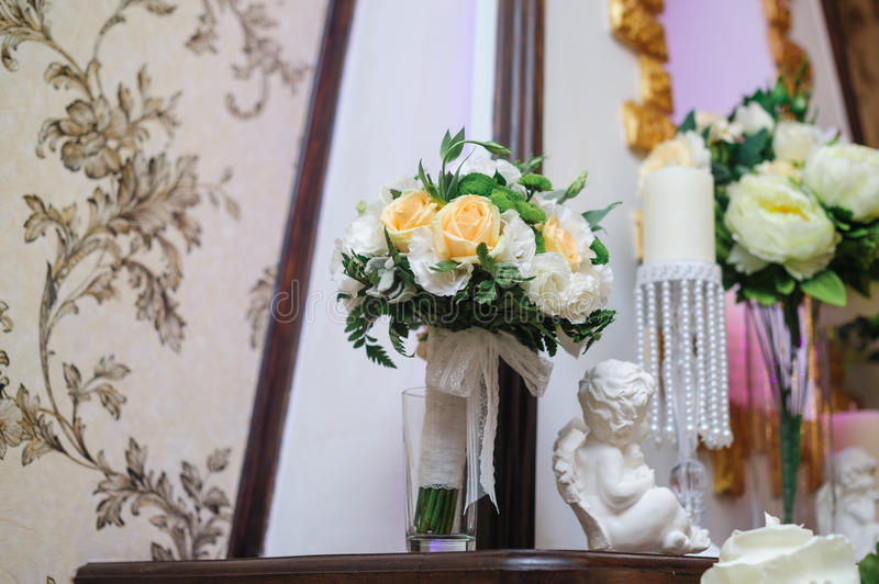 Beautiful bridal bouquet of white and yellow flowers in the interior.  royalty free stock photography