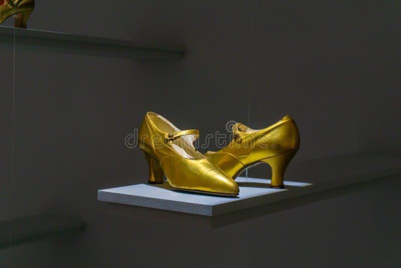 Beautiful bridal high and thin golden stiletto heel shoes. Luxury designer wedding shoes on the shelf royalty free stock image