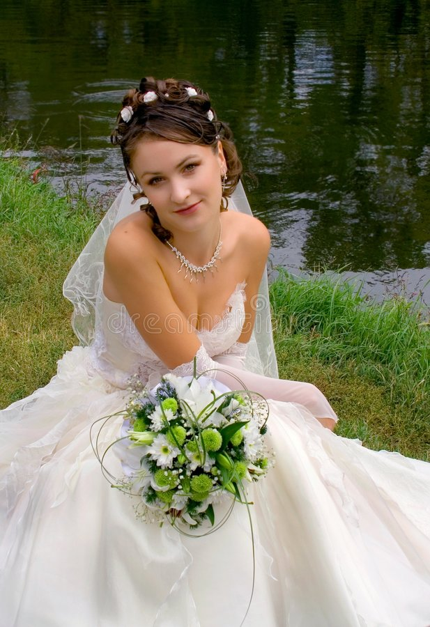 Brunette bride by the water stock photos