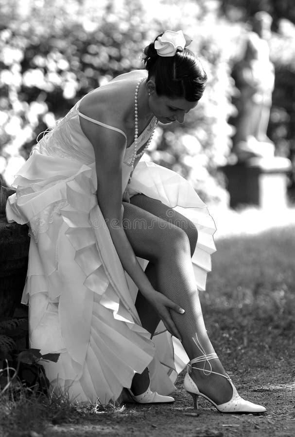 Beautiful bride adjusting her stockings stock image