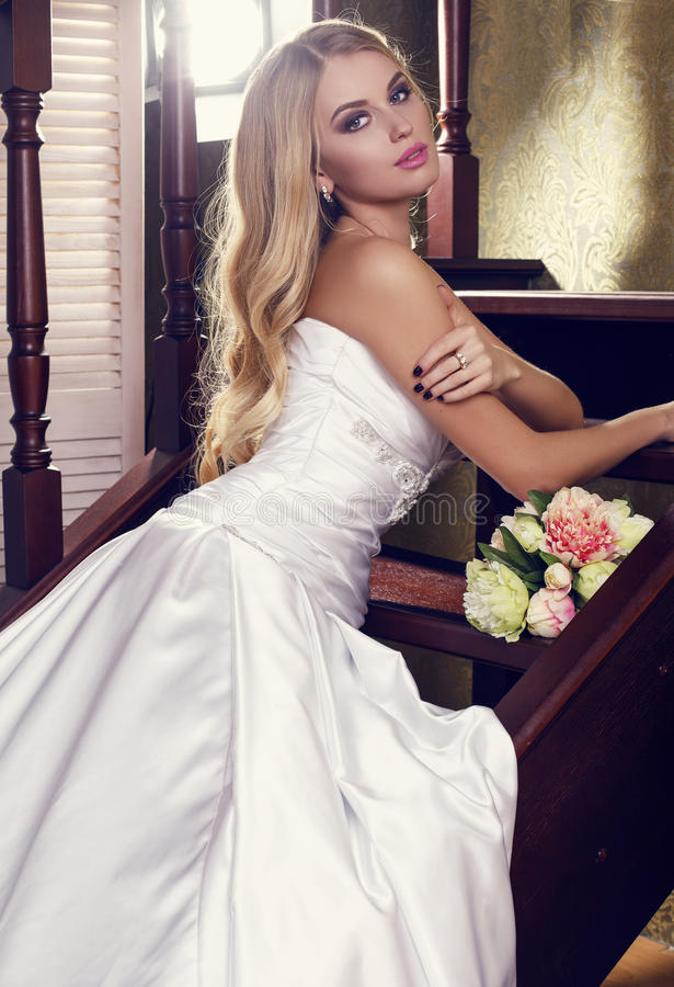 Beautiful bride with blond hair in elegant wedding dress with bouquet stock photo