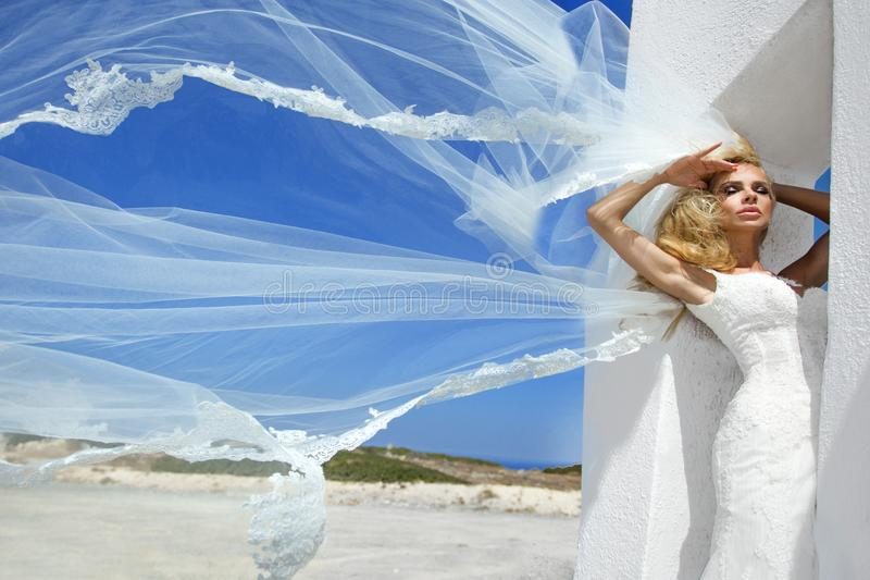 Beautiful bride blonde female model in amazing wedding dress poses on the island of Santorini in Greece royalty free stock photography