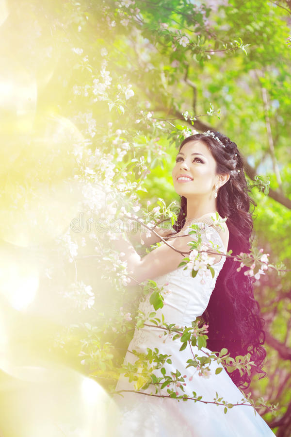 Beautiful bride in a blossoming garden royalty free stock photo