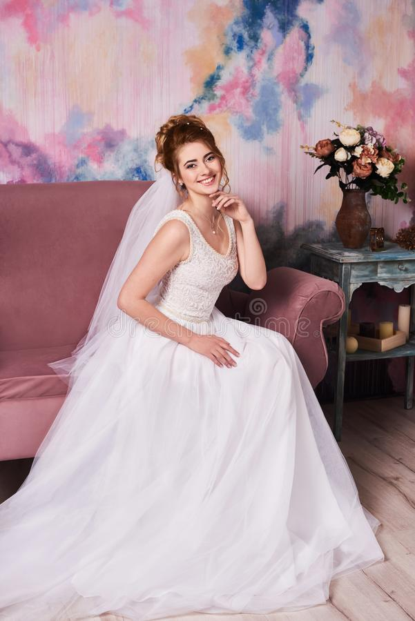 Young beautiful bride getting ready for wedding photo shoot, she waiting for groom stock photo