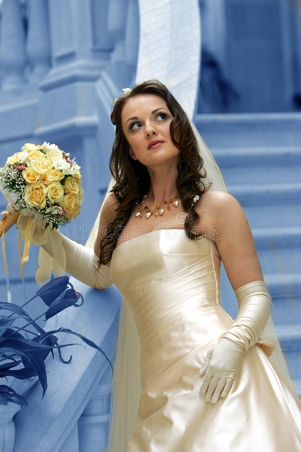 Beautiful bride with bouquet. Low angle view of beautiful young bride with bouquet of flowers, blue background royalty free stock image