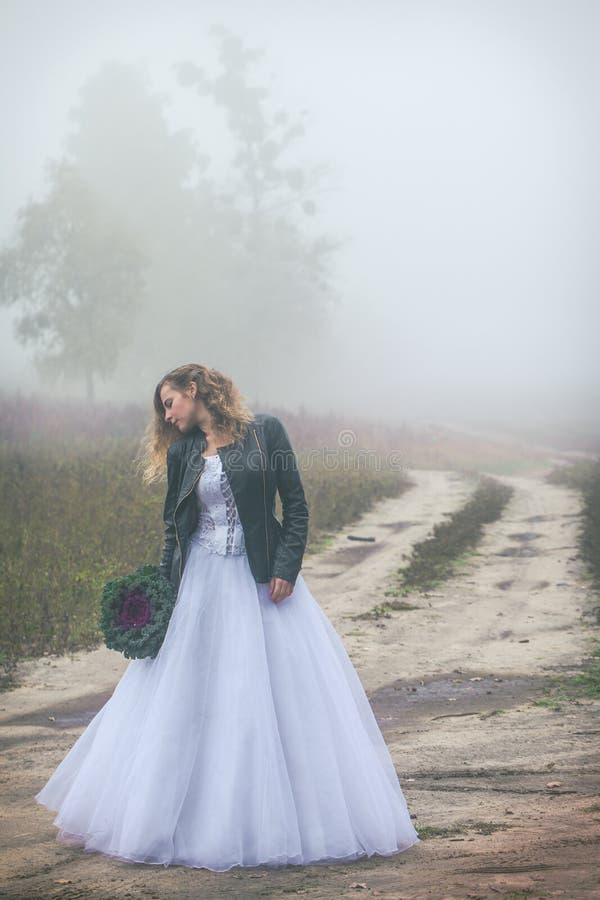 Sad bride near a dirt road royalty free stock photo