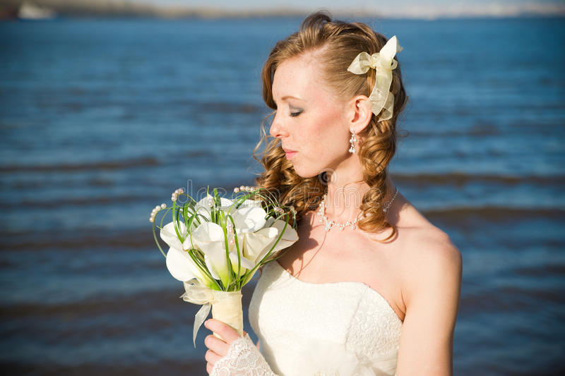 Beautiful bride with a bouquet of calla lilies on coast of river royalty free stock photography