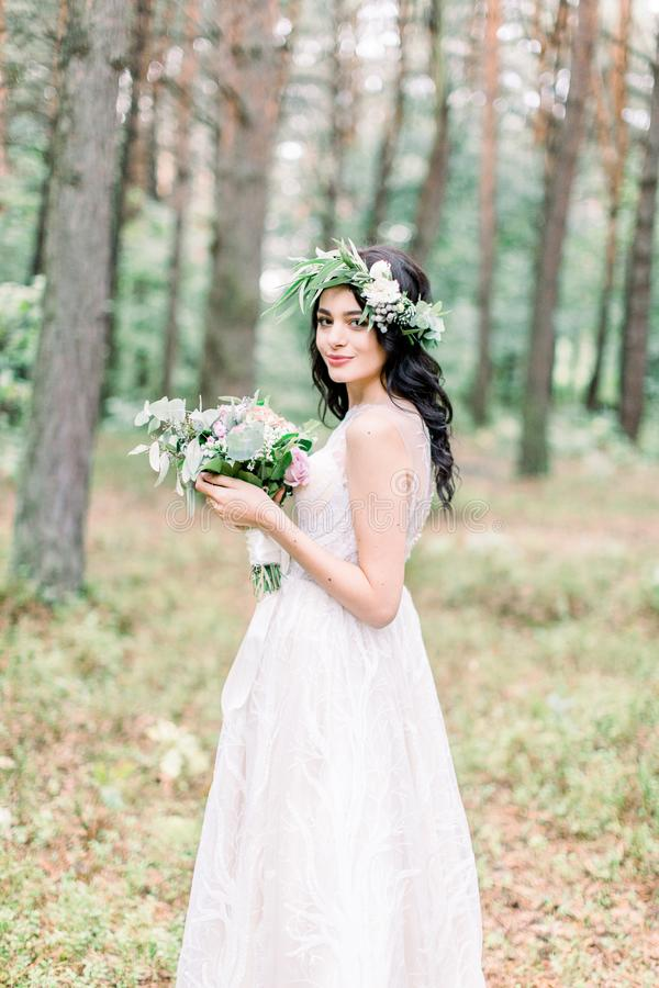 Beautiful bride with bouquet of flowers in white dress stands on forest background. Rustic style royalty free stock photos