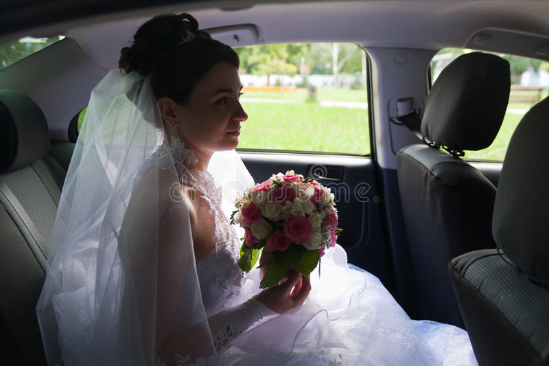 Beautiful bride in a car window. With bouquet stock photography