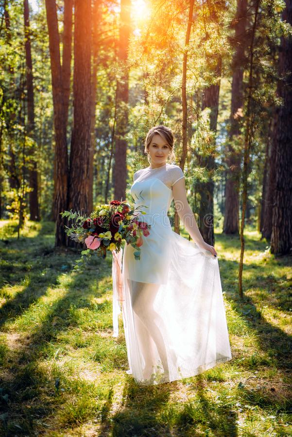 Beautiful bride with colorful wedding bouquet in her hands outdoors. Cute bride in lace dress in a green Park. Happy smiling bride stock photos