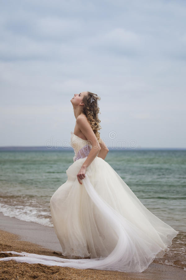 Beautiful bride dancing on the beach royalty free stock photo